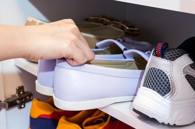 Młoda kobieta podnosi dworskich buty w gabinecie