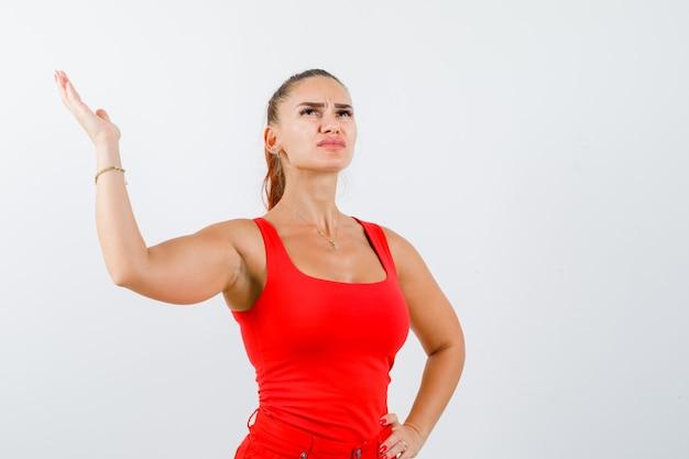 Młoda kobieta podnosi rękę, trzymając rękę na biodrze w czerwonym podkoszulku, spodniach i zamyślonym spojrzeniu. przedni widok.