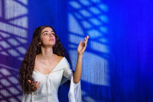 Młoda kobieta podnosi rękę z prośbą w kolorze białym, na niebieskim