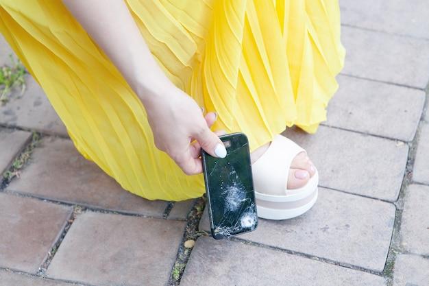 Młoda kobieta podnosi z ziemi zepsuty telefon