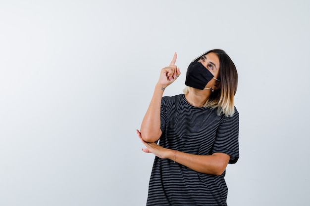 Młoda kobieta, podnosząc palec wskazujący w geście eureki, trzymając rękę pod łokciem w czarnej sukience, czarnej masce i patrząc rozsądnie, widok z przodu.