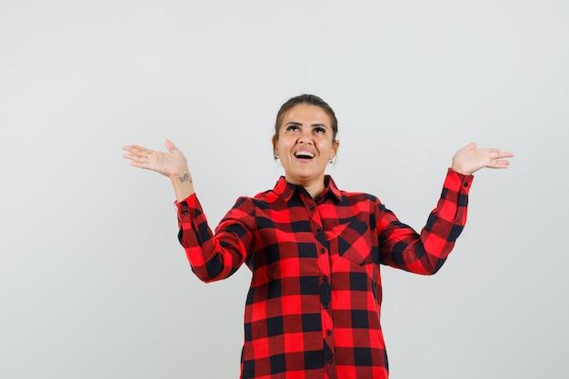 Młoda kobieta, podnosząc ręce, trzymając coś w kraciastej koszuli i patrząc zadowolony. przedni widok.
