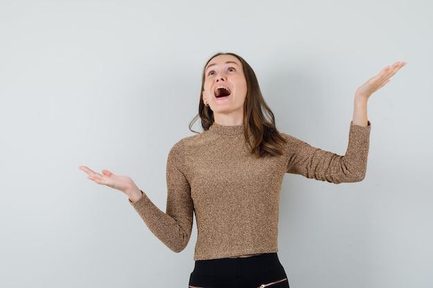 Młoda kobieta podnosząc ręce z otwartą dłonią w złotą bluzkę i patrząc zdziwiony, widok z przodu.