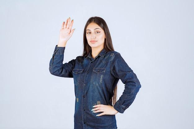 Młoda kobieta, podnosząc rękę, aby zwrócić na siebie uwagę