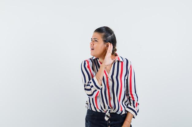 Młoda kobieta, podnosząc rękę, próbując usłyszeć w bluzce w paski i patrząc skoncentrowany