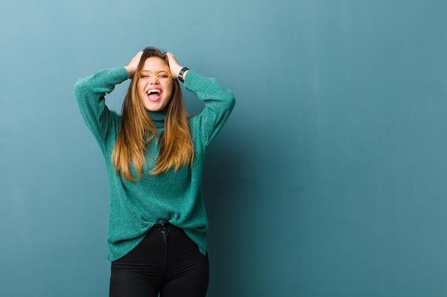 Młoda kobieta podnosząca ręce do głowy, z otwartymi ustami, czująca się wyjątkowo szczęśliwa, zdziwiona, podekscytowana i szczęśliwa