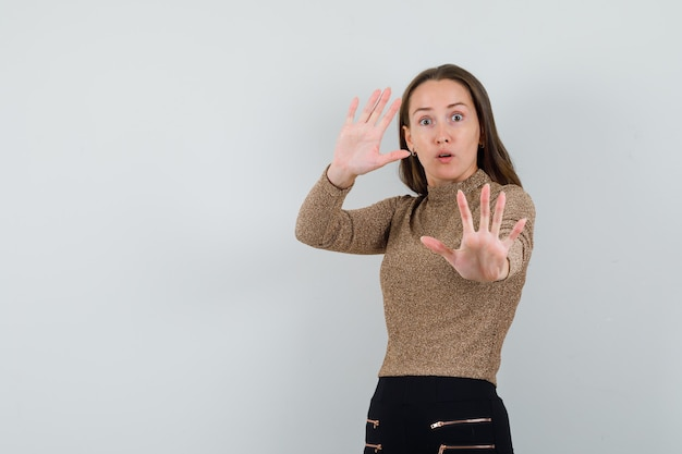 Młoda kobieta podnosząca ręce do obrony w złotej bluzce i wyglądająca na zmartwioną. przedni widok. miejsce na tekst
