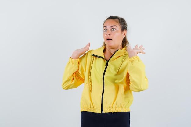 Młoda kobieta podnosząca ręce do obrony w żółtym płaszczu przeciwdeszczowym i wyglądająca na przestraszoną