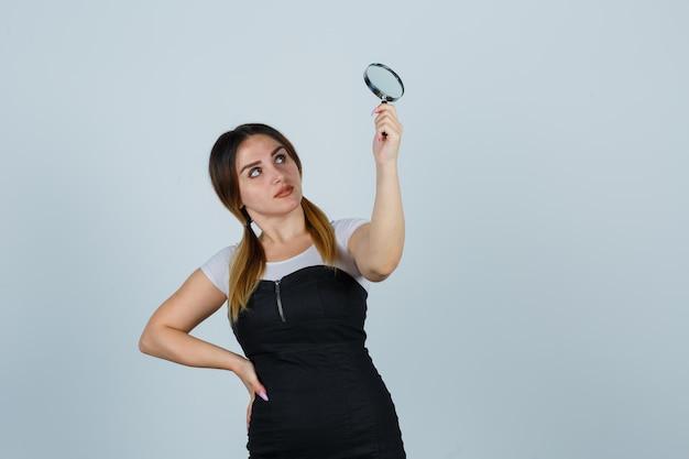 Młoda kobieta podnosząca szkło powiększające