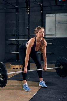 Młoda kobieta podnoszenia brzana w siłowni