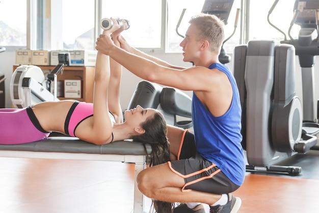 Młoda kobieta podnoszenie ciężarów treningu wspomagana przez jej trenera na siłowni