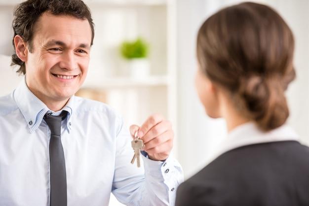 Młoda kobieta podpisuje umowę finansową z męskim pośrednikiem w handlu nieruchomościami.