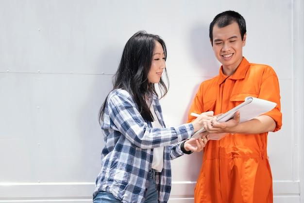 Młoda kobieta podpisywania dostawy w schowku obok mężczyzny dostawy