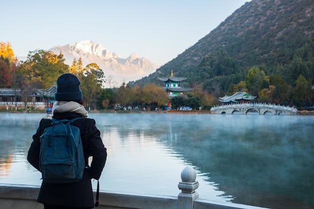 Młoda kobieta podróżniczka podróżująca w basenie black dragon z jade dragon snow mountain, punktem orientacyjnym i popularnym miejscem atrakcji turystycznych w pobliżu starego miasta w lijiang. lijiang, yunnan, chiny