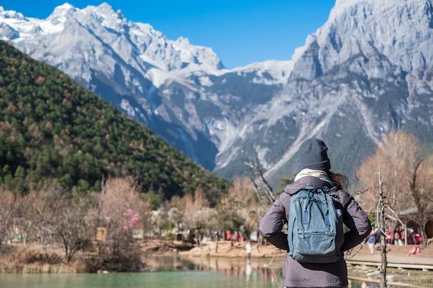 Młoda kobieta podróżniczka podróżująca w dolinie blue moon, charakterystycznym i popularnym miejscu w jade dragon snow mountain mountain scenic area, w pobliżu lijiang old town. lijiang, yunnan, chiny. koncepcja podróży solo