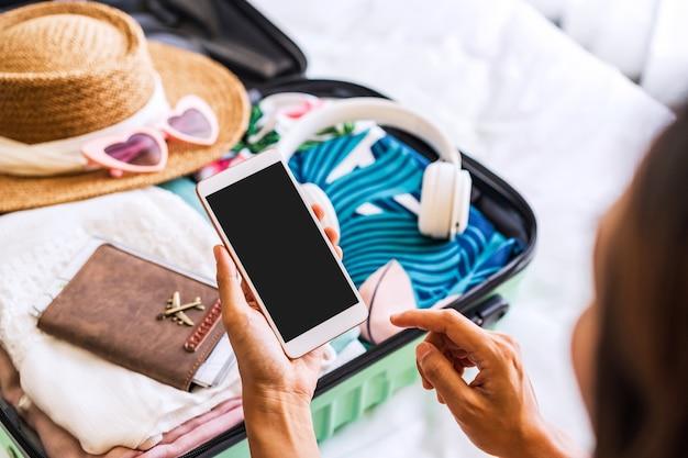Młoda kobieta podróżniczka siedzi na łóżku za pomocą smartfona i pakuje walizkę, przygotowując się do podróży na letnie wakacje