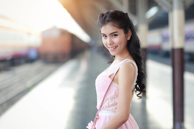 Młoda kobieta podróżnik czeka na pociąg