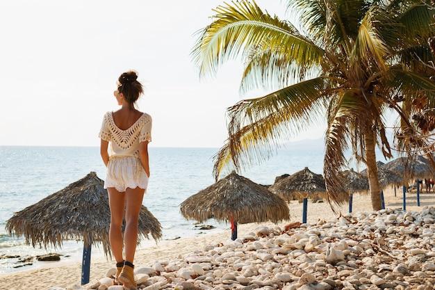 Młoda kobieta podróżnik na plaży z kamieniami i palmami