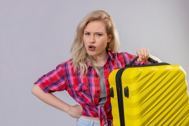 Młoda kobieta podróżnik na sobie czerwoną koszulę, trzymając walizkę na na białym tle białej ścianie
