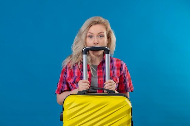 Młoda kobieta podróżnik na sobie czerwoną koszulę, trzymając walizkę na na białym tle niebieskiej ścianie