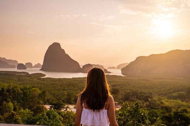 Młoda kobieta podróżnik patrząc na wschód słońca nad górą w samet nang ona, tajlandia