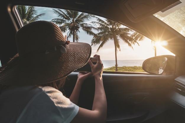 Młoda kobieta podróżnik patrzeje fotografię i bierze fotografię pięknego zmierzch przy plażą wśrodku samochodu