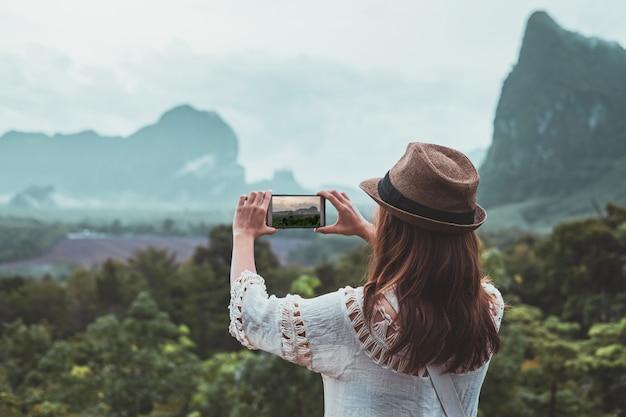 Młoda kobieta podróżnik patrzeje fotografię z smartphone i bierze przy pięknym widokiem
