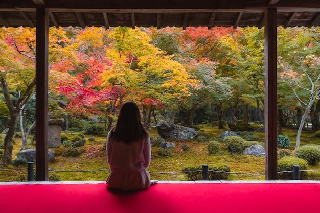Młoda kobieta podróżnik patrzeje piękną jesień w japonia, podróż stylu życia pojęcie