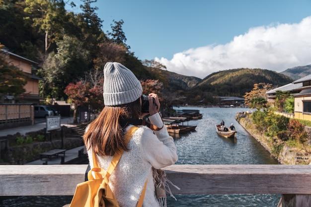 Młoda kobieta podróżnik patrzeje pięknego krajobraz przy arashiyama japonia, podróż stylu życia pojęcie