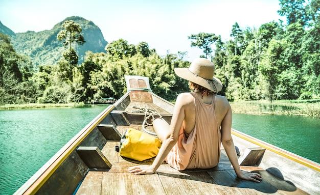 Młoda kobieta podróżnik podczas rejsu łodzią longtail na wyspie skaczącej po jeziorze cheow lan lan