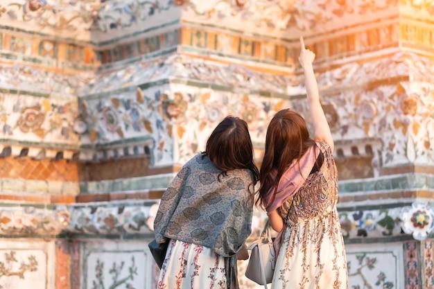 Młoda kobieta podróżnik podróżuje w wata arun ratchawararam ratchawaramahawihan świątyni w bangkok