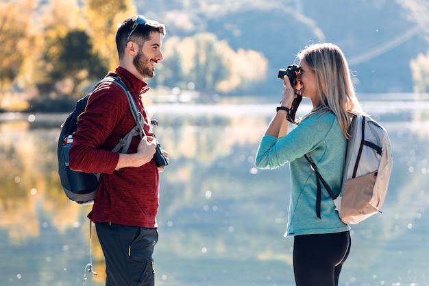 Młoda kobieta podróżnik robienia zdjęć do swojego chłopaka przed jeziorem w górach.