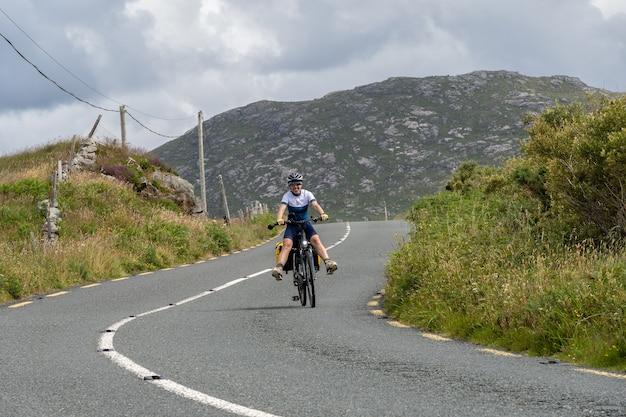 Młoda kobieta podróżnik rowerzysta uśmiechający się na trasie connemara galway irlandia