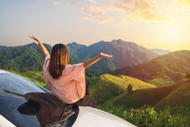 Młoda kobieta podróżnik siedzi na samochodzie, oglądając piękny widok na góry podczas podróży jazdy samochodem na wakacje