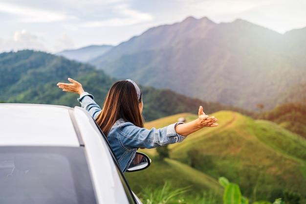 Młoda kobieta podróżnik siedzi w samochodzie, oglądając piękny widok na góry podczas podróży jazdy samochodem na wakacje