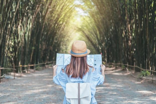Młoda kobieta podróżnik szuka kierunku na mapie lokalizacji podczas podróży