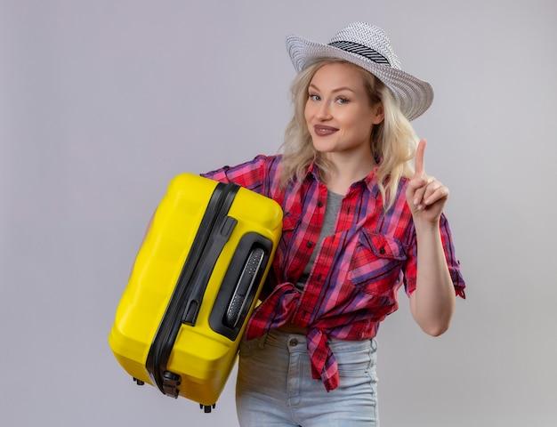 Młoda kobieta podróżnik ubrana w czerwoną koszulę w kapeluszu, trzymając walizkę wskazuje na odizolowaną białą ścianę