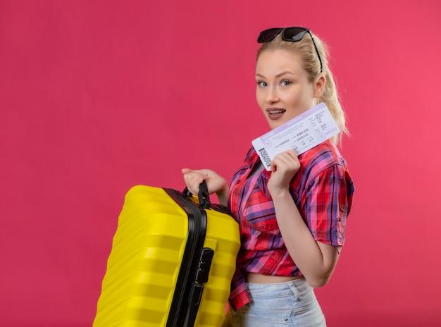Młoda kobieta podróżnik ubrana w czerwoną koszulę w okularach, trzymając walizkę i bilet na na białym tle różowej ścianie