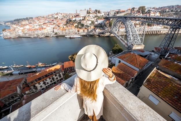 Młoda kobieta podróżnik w kapeluszu, ciesząc się pięknym widokiem na gród z lotu ptaka z rzeką douro i mostem luise podczas porannego światła w porto, portugalia