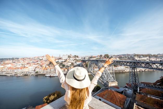 Młoda kobieta podróżnik w kapeluszu przeciwsłonecznym z podniesionymi rękami, ciesząc się pięknym widokiem na panoramę miasta z rzeką douro i mostem luise podczas porannego światła w porto, portugalia
