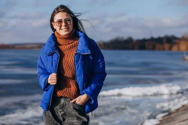 Młoda kobieta podróżnik w niebieskiej marynarce na plaży