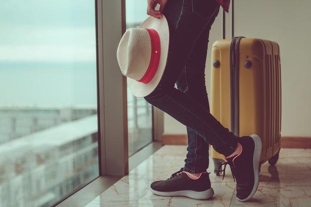 Młoda kobieta podróżnik w przypadkowych ubraniach z żółtą walizką