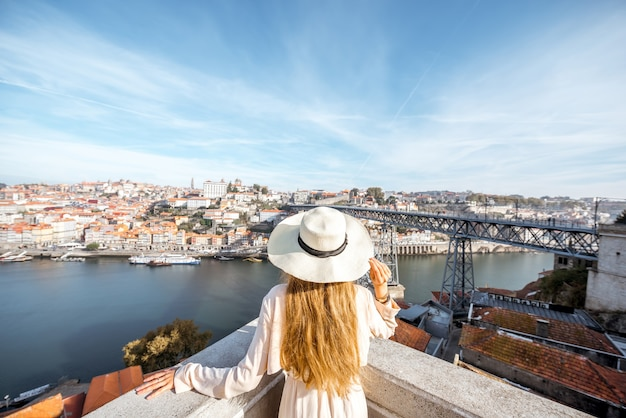 Młoda kobieta podróżnik w sunhat stojący z powrotem na tle piękne antenowe gród z rzeką douro i mostem luise podczas porannego światła w porto, portugalia