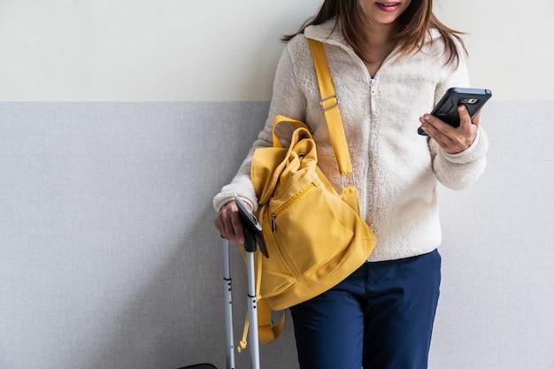 Młoda kobieta podróżnik z bagażem i plecakiem używać smartphone przy lotniskiem