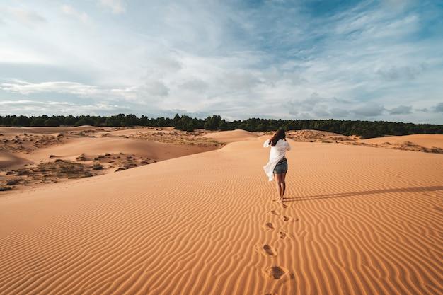 Młoda kobieta podróżnika odprowadzenie przy czerwonymi piasek diunami w wietnam, podróż stylu życia pojęcie