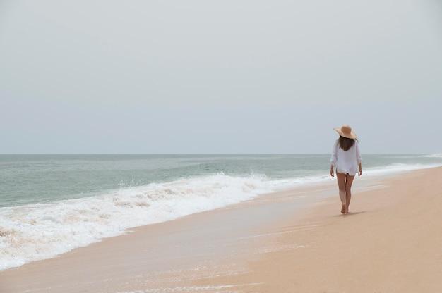 Młoda kobieta podróżująca bez covid nad morzem