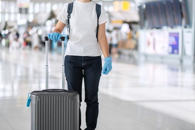 Młoda kobieta podróżująca w rękawicy nitrylowej, trzymając uchwyt bagażu w terminalu lotniska