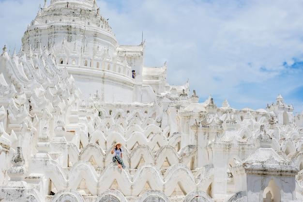 Młoda kobieta podróżująca z torbą odwiedza hsinbyume pagoda lub dzwoni białego taj mahal irrawaddy rzeka, lokalizować w mingun, sagaing region blisko mandalay, myanmar. punkt orientacyjny i popularny
