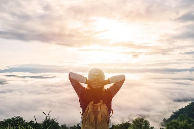 Młoda kobieta podróżujących patrząc na wschód słońca i morze mgły na górze rano