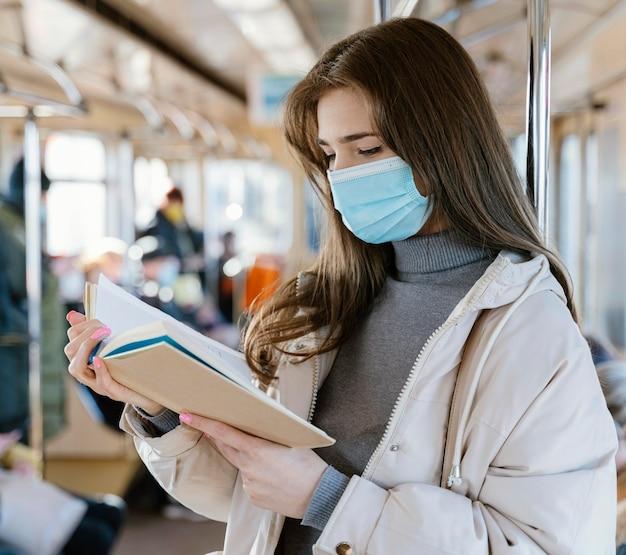 Młoda kobieta podróżuje metrem, czytając książkę